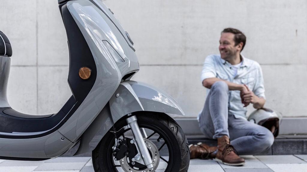 man next to Kumpan scooter