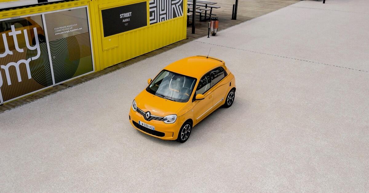 Oranje Renault Twingo naast container
