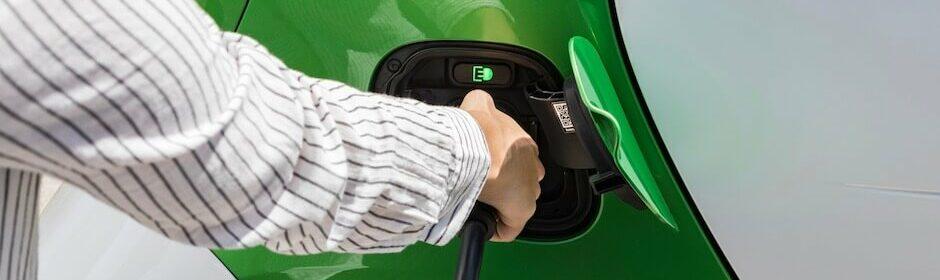 vrouw plugt elektrische auto in