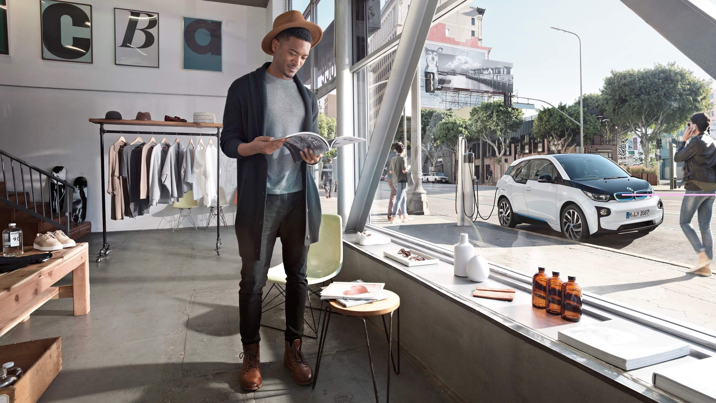 gekleurde hipster man laadt BMW i3 op